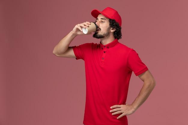 Vooraanzicht mannelijke koerier bezorger in rood shirt en cape koffie drinken op roze muur service uniforme levering werknemer baan werknemer mannelijke werk