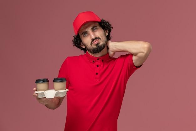 Vooraanzicht mannelijke koerier bezorger in rood shirt en cape met bruine bezorging koffiekopjes met nekpijn op lichtroze muur dienstverlener