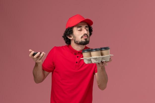 Vooraanzicht mannelijke koerier bezorger in rood shirt en cape met bruine bezorging koffiekopjes ruiken aan lichtroze muur service bezorging baan werknemer