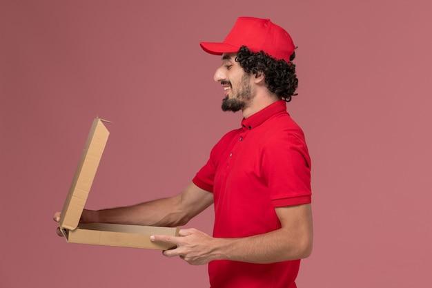 Vooraanzicht mannelijke koerier bezorger in rood shirt en cape met lege voedseldoos op de roze muur werknemer van het dienstverleningsbedrijf