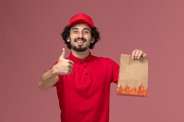 Vooraanzicht mannelijke koerier bezorger in rood shirt en cape met voedselpakket en lachend op roze muur service bezorgbedrijf werknemer