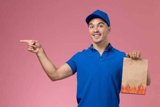 Vooraanzicht mannelijke koerier in blauw uniform bedrijf papieren pakket met glimlach op roze muur, baan werknemer uniforme dienstverlening