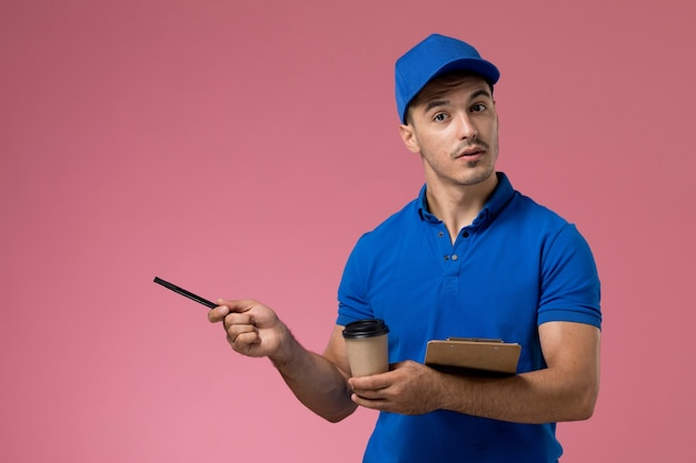 Vooraanzicht mannelijke koerier in blauw uniform bedrijf pen koffie samen met blocnote op de roze muur, werknemer uniforme dienstverlening