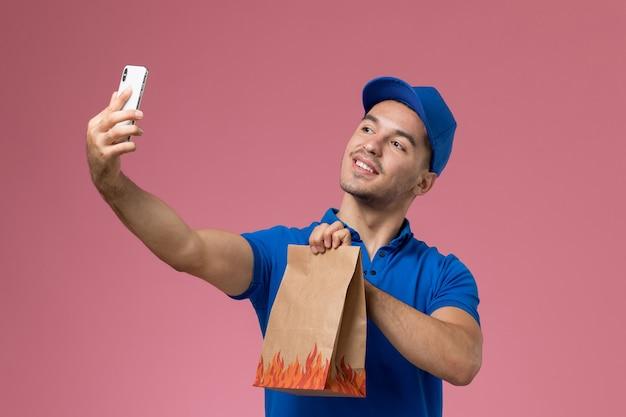 Vooraanzicht mannelijke koerier in blauw uniform die een selfie met voedselpakket op roze muur, uniforme levering van de dienst van de baanmedewerker neemt