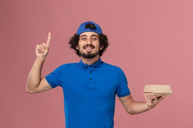 Vooraanzicht mannelijke koerier in blauw uniform en cape die weinig voedselpakket met opgeheven vinger op roze muur houdt