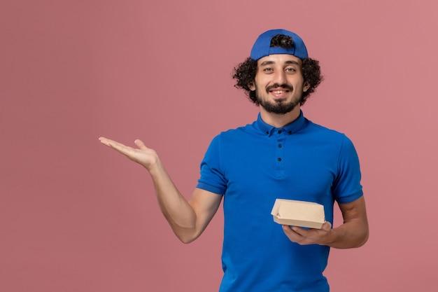 Vooraanzicht mannelijke koerier in blauw uniform en cape die weinig voedselpakket voor bezorging op de roze muur houdt