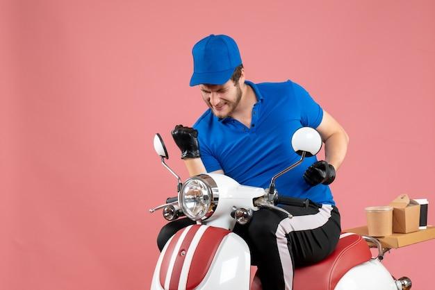 Vooraanzicht mannelijke koerier in blauw uniform en handschoenen die zich verheugen over roze kleur werk fastfood fietsservice voedselbezorging