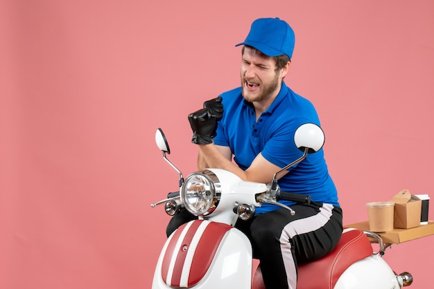 Vooraanzicht mannelijke koerier in blauw uniform en handschoenen op de roze kleur werk fastfood service food job bezorgfiets