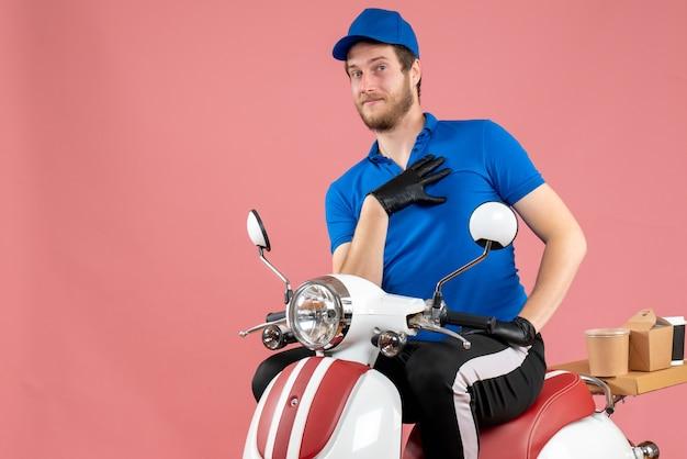 Vooraanzicht mannelijke koerier in blauw uniform en handschoenen op roze kleur werk fastfood service eten bezorgfiets