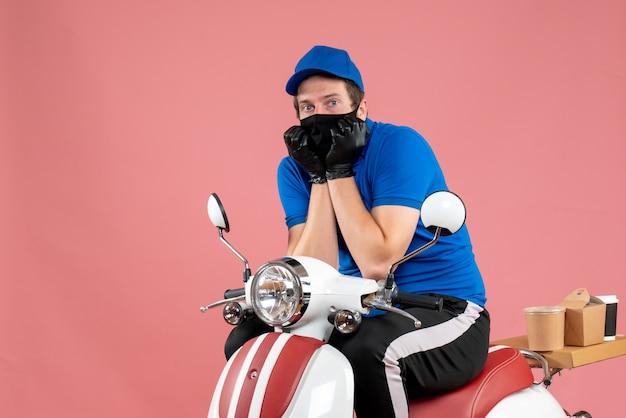 Vooraanzicht mannelijke koerier in blauw uniform en masker bang voor roze voedselbaan fastfoodservice bezorgfiets viruswerk covid-