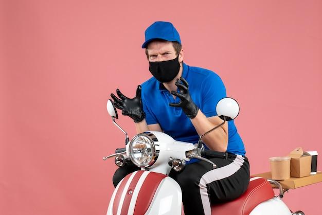 Vooraanzicht mannelijke koerier in blauw uniform en masker boos op roze voedselbaan fastfoodservice bezorgfiets viruswerk covid-