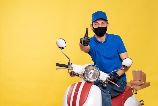 Vooraanzicht mannelijke koerier in blauw uniform en masker lachen op gele baan fiets covid- pandemie levering virus service werk