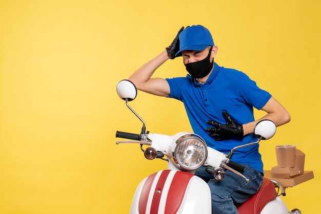Vooraanzicht mannelijke koerier in blauw uniform en masker met hartzeer op geel werk covid- levering pandemie fietsservice baanvirus