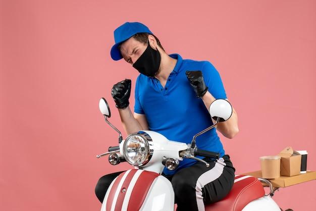 Vooraanzicht mannelijke koerier in blauw uniform en masker op een roze service fastfood covid- werkbezorgingsbaan virus fietskleur
