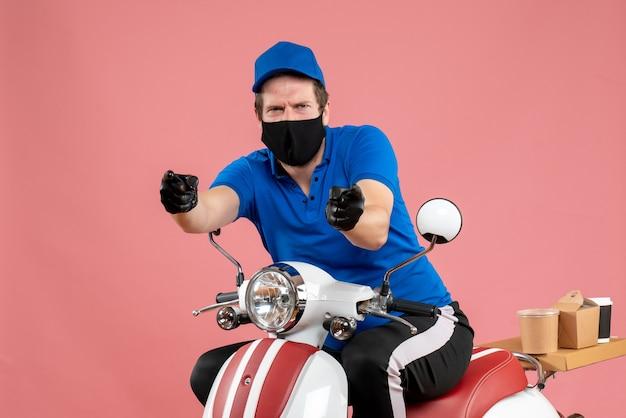 Vooraanzicht mannelijke koerier in blauw uniform en masker op een roze service fastfood covid- werkbezorgingsbaan virusfiets