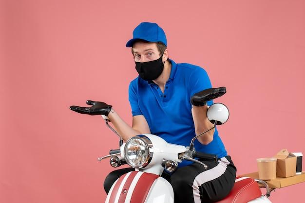 Vooraanzicht mannelijke koerier in blauw uniform en masker op roze baanbezorging fastfood fietswerk covid voedselvirusservice