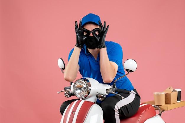 Vooraanzicht mannelijke koerier in blauw uniform en masker op roze baanbezorging fastfoodservice fiets covid-food virus