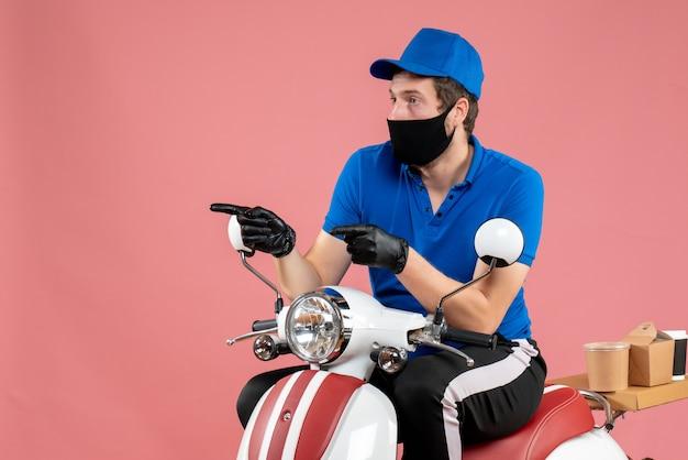 Vooraanzicht mannelijke koerier in blauw uniform en masker op roze baanbezorging fastfoodservice fietswerk covid-food virus