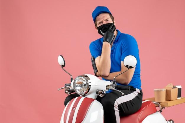 Vooraanzicht mannelijke koerier in blauw uniform en masker op roze bezorgingsvirus voedsel fastfoodservice fietswerk covid-job