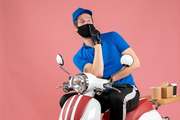 Vooraanzicht mannelijke koerier in blauw uniform en masker op roze bezorgvirus fastfoodservice fiets covid-job food
