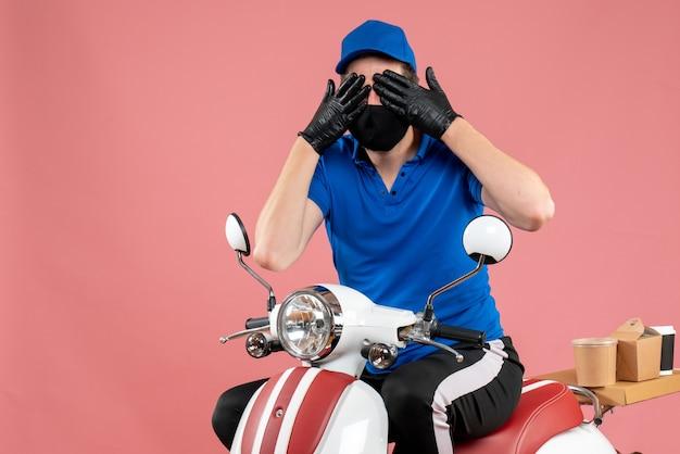 Vooraanzicht mannelijke koerier in blauw uniform en masker op roze service fastfood covid- bezorgingsbaan virus fietskleur