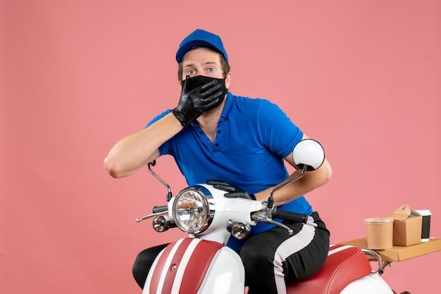 Vooraanzicht mannelijke koerier in blauw uniform en masker op roze service fastfood covid- bezorgingsbaan virusfiets