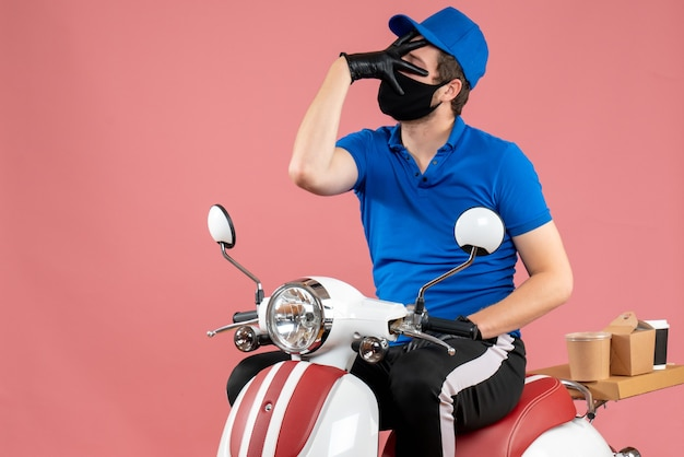 Vooraanzicht mannelijke koerier in blauw uniform en masker op roze virus fastfoodservice fietswerk covid-bezorgingsbaan