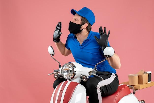 Vooraanzicht mannelijke koerier in blauw uniform en masker op roze virusvoedselbaan fastfoodservice fietswerk covid levering