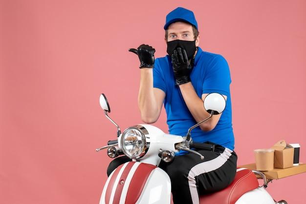 Vooraanzicht mannelijke koerier in blauw uniform en masker op roze voedselbaan fastfoodservice bezorgfiets viruswerk covid-