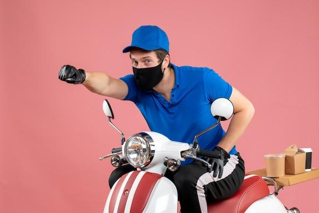 Vooraanzicht mannelijke koerier in blauw uniform en masker op roze voedselbaan werk fastfood bezorgfiets virus covid-