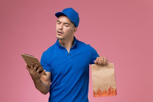 Vooraanzicht mannelijke koerier in blauw uniform met blocnote voedselpakket op de roze muur, uniforme dienstverlening