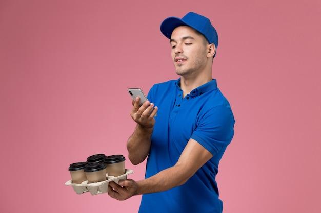 Vooraanzicht mannelijke koerier in blauw uniform met een shoot van koffiekopjes op roze muur, werknemer uniforme dienstverlening