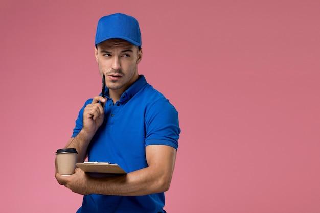 Vooraanzicht mannelijke koerier in blauw uniform met kleine blocnote en koffie denken aan roze muur, levering van de werknemer uniforme dienstverlening