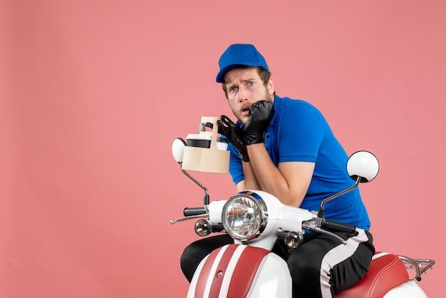 Vooraanzicht mannelijke koerier in blauw uniform met koffie bang op roze baankleur fastfood werk bezorgfiets servicemedewerker