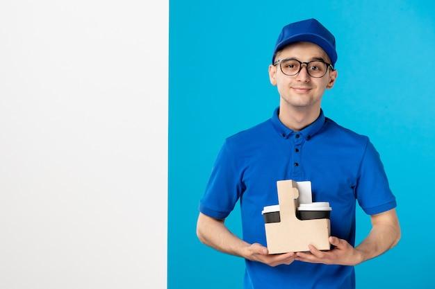 Vooraanzicht mannelijke koerier in blauw uniform met koffie op een blauw