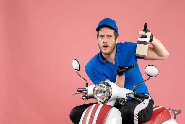 Vooraanzicht mannelijke koerier in blauw uniform met koffie op roze kleuren baan fastfood service werknemer levering werk fiets