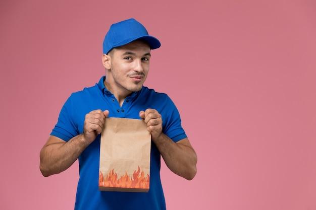Vooraanzicht mannelijke koerier in blauw uniform met papieren pakket op de roze muur, uniforme dienstverlening van baanarbeider