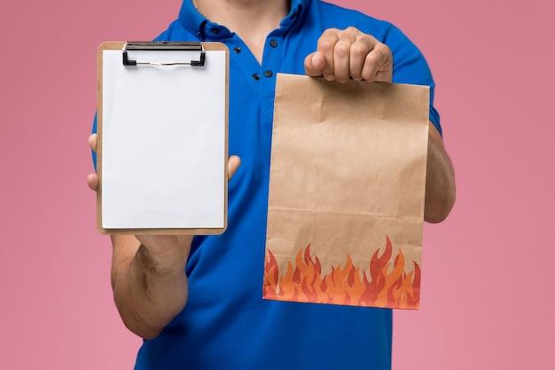 Vooraanzicht mannelijke koerier in blauw uniform met papieren voedselpakket en blocnote op de roze muur, uniforme dienstverlening