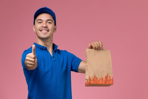 Vooraanzicht mannelijke koerier in blauw uniform met papieren voedselpakket op de roze muur, levering van arbeiders uniforme dienstverlening