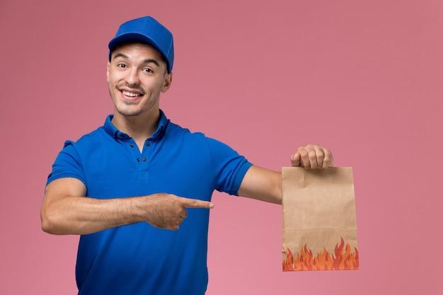 Vooraanzicht mannelijke koerier in blauw uniform met papieren voedselpakket op de roze muur, uniforme dienstverlening