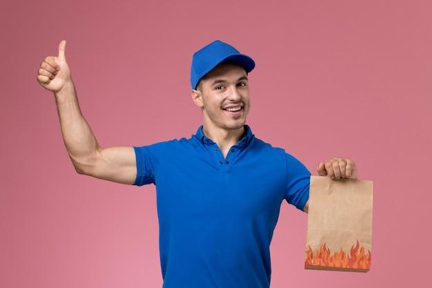 Vooraanzicht mannelijke koerier in blauw uniform met voedselpakket dat als teken op de roze muur, levering van de dienst van de baanarbeider toont