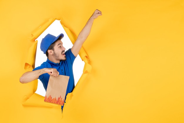 Vooraanzicht mannelijke koerier in blauw uniform met voedselpakket in superman pose op gele ruimte