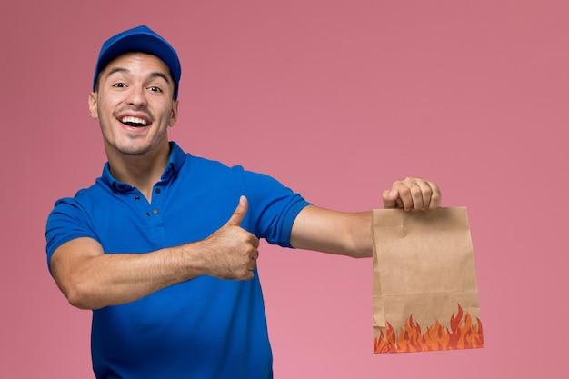 Vooraanzicht mannelijke koerier in blauw uniform met voedselpakket lachend op de roze muur, uniforme levering van de servicebaan