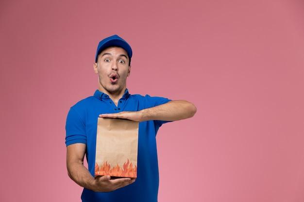 Vooraanzicht mannelijke koerier in blauw uniform met voedselpakket met grappige uitdrukking op roze muur, uniforme dienstverlening van baanarbeider