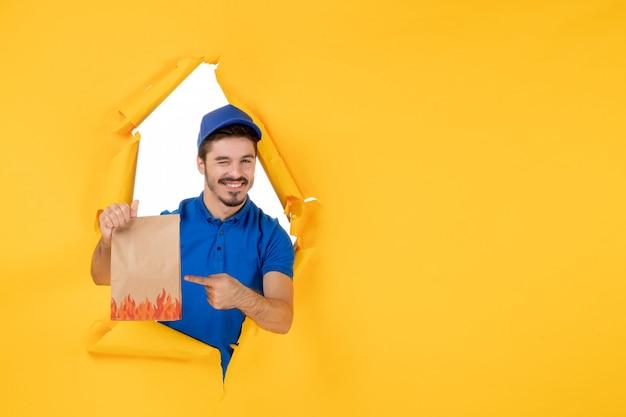 Vooraanzicht mannelijke koerier in blauw uniform met voedselpakket op gele bureaubezorgdienstmedewerker fotokleurenwerk