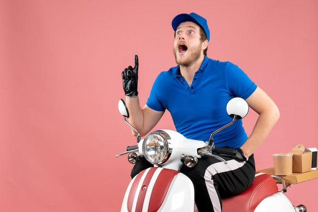 Vooraanzicht mannelijke koerier in blauw uniform op een roze voedsel fast-food service fiets bezorg baan kleur werk
