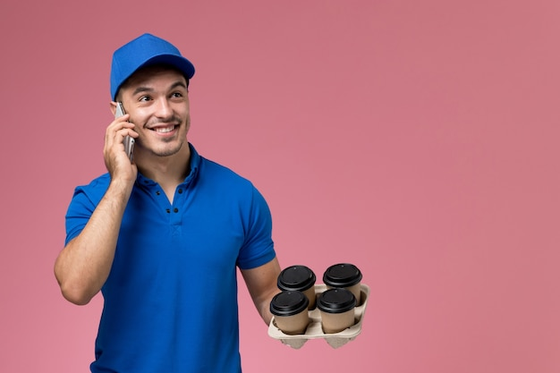 Vooraanzicht mannelijke koerier in blauw uniform praten aan de telefoon met koffie op roze muur, uniforme levering van de dienst van de baanarbeider