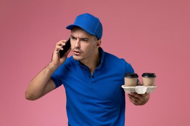 Vooraanzicht mannelijke koerier in blauw uniform praten aan de telefoon met koffiekopjes op roze muur, uniforme dienstverlening