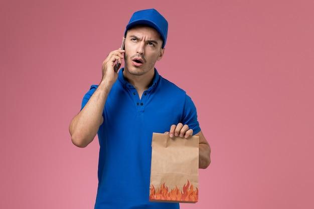 Vooraanzicht mannelijke koerier in blauw uniform praten aan de telefoon op roze muur, uniforme levering van baanmedewerker