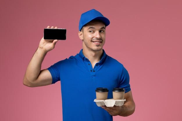Vooraanzicht mannelijke koerier in blauw uniform telefoonkoffie te houden en lachend op roze muur, baan werknemer uniforme dienstverlening